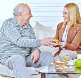 caregiver giving food the senior man